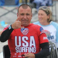 "Chaka smiles and wears a red, USA Surfing wet suit while giving a ""hang loose"" sign."