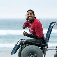 Jose smiles on the beach in a wheelchair.