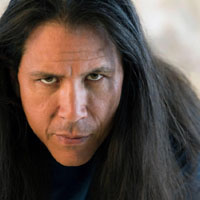 Long, dark hair frames the face of Sensei William Ford as he stares with an intense gaze.