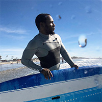 Ty Duckett holds a blue surfboard while staring toward the ocean.