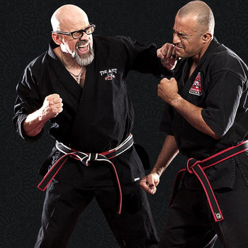 John Hackleman is dressed in a black martial arts uniform and is seen punching another martial artist in the jaw.