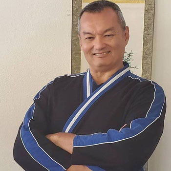 Grandmaster Scot Conway, dressed in a black and blue martial arts uniform, smiles while crossing his arms over his chest.