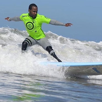 Ty Duckett catches a wave on his surfboard with his arms spread wide and his prosthetic leg forward.
