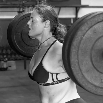 A B&W photo of Angi Sanders as she lifts heavy wihle doing barbell squats.