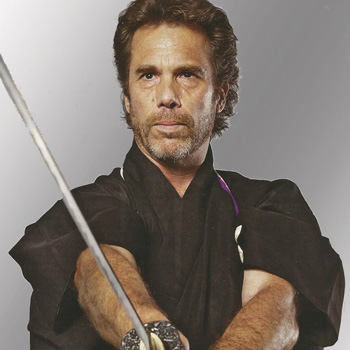 Master Dana Abbott is shown in a black martial arts uniform while wielding a large sword.