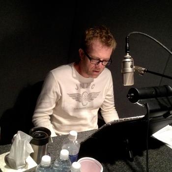 Scott Brick speaks into a microphone inside of a studio.