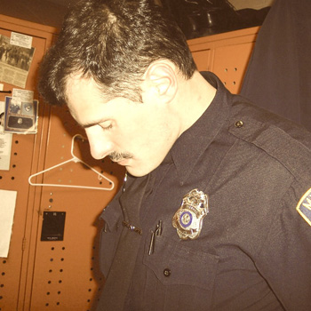 A younger Jason James stands beside a locker in his police uniform.