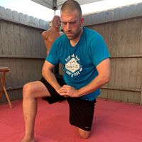 Joshua Loya kneels post-workout with hands in the GKKD bow.