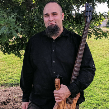 Josh Wolfer holds a tobacco-colored bass guitar while smiling and standing beneath a tree.