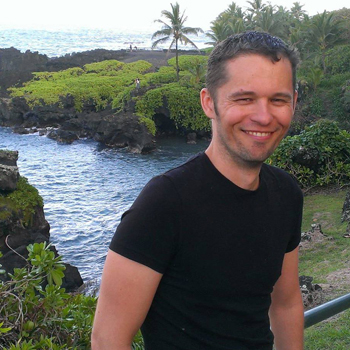Kevin Cole smiles in front of a scenic ocean view in Wai'anapanapa State Park.