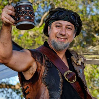 A smiling Daniel O'Ryan in Renaissance attire toasts a wooden beer mug.
