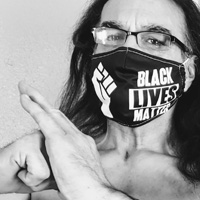 Michael Mendoza, wearing a Black Lives Matter face mask, holds a kempo bow.