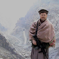 Col Robert W Redding wears tan Afghan clothing while standing on a mountain-lined road between Kabul and Jalalabad.