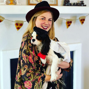 Bianca Wulwick, wearing a dark fedora and floral tunic blouse, smiles while holding her Cavalier King Charles Spaniel named Bourdain.