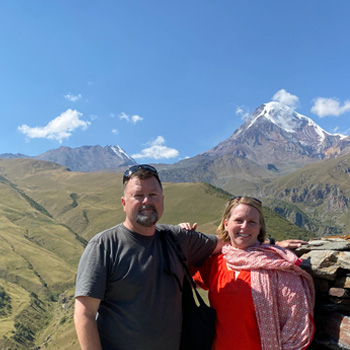 Col Robert W Redding stands with his wife in front of Mount Kazbek at the Gergeti Trinity Church.