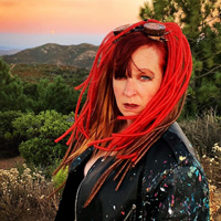 """Heather Meglasson gives a sultry look to the camera dressed as her """"Shadow Warrior"""" character wearing a disheveled wig of red cables and a black leather jacket splattered with paint."""