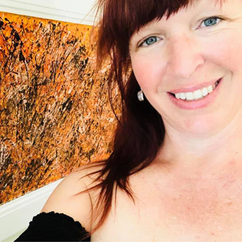 Heather Meglasson smiles warmly in front of abstract, splattered artwork made up of orange, black and white colors.