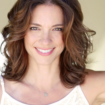 Nicol Zanzarella smiles pleasantly with her brown hair framing her face.