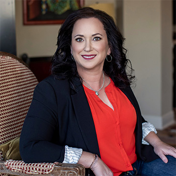 Simone Knego sits in a chair smiling pleasantly dressed in an orange blouse with blue blazer.