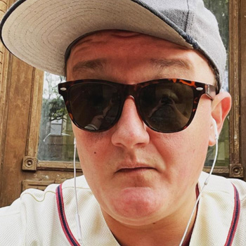 Will Macarro sits on the front porch wearing a baseball cap, jersey and sunglasses.